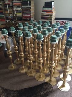 "Wedding centerpieces made from two 9"" wooden candlesticks, circular base, gold spray paint and floral foams."