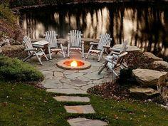 Adirondack chairs circle a firepit