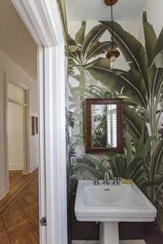 bathroom wallpaper In the small bathroom, the team broke with the neutral scheme. The pendant light is by woodworker Emily Brock and the leaf-print wallpaper is by French company Ananbo. Palm Wallpaper, Tropical Wallpaper, Bathroom Wallpaper, Print Wallpaper, Wallpaper Toilet, Botanical Wallpaper, Tropical Home Decor, Tropical Interior, Tropical Houses
