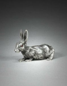 A Fabergé gem-set silver bell-push in the form of a rabbit, Moscow, 1896-1908 naturalistically cast, chased, and engraved in a crouching position, its ears cocked, the sprung cabochon ruby eyes as push-pieces, marked 'K. Fabergé' beneath Imperial Warrant on the back right foot, 84 standard.