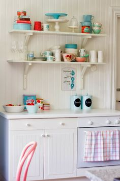White cabinets, beadboard, open shelving, colorful painted chairs