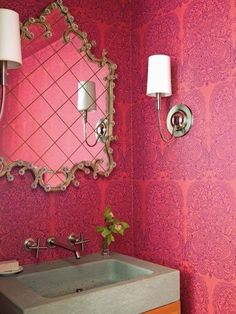 Orange and pink powder room boasts walls clad in orange and pink damask wallpaper lined with an ornate mirror over an orange washstand with concrete sink.
