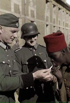 A colored photo of two German soldiers lighting a cigarette for a African POW serving as a colonial soldier in the French Army. Photo taken around 1940 in France.