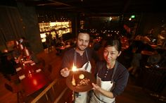 David Myers, chef and owner, and Kuniko Yagi, executive chef at Hinoki & the Bird, hold a plate of hinoki-scented black cod at the new restaurant, at the base of a Century City condo tower.
