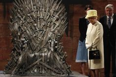 Britain's Queen Elizabeth looks at the Iron Throne as she meets members of the cast on the set of the television show Game of Thrones in the Titanic Quarter of Belfast, Northern Ireland, June 24, 2014