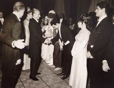 H.I.M. the Shah of Iran and Empress Farah Pahlavi receiving the artists in private audiences From the right: Ahmad Pejman, Monir Vakili, Enayat Rezai, Hossein Sarshar, Bahman Mofid, and Afsaneh Deyheem (fourth and fifth less visibly). Inauguration of Roudaki Hall, Tehran, October 26, 1967. Photo courtesy of Enayat Rezai