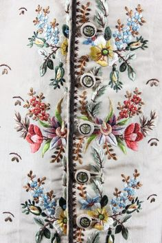 Detail embroidery, waistcoat, c. 1790. Cream silk faille brightly embroidered with floral garlands, brown silk sprigged ground, the linen back with two draw-string bands to tighten at waist.