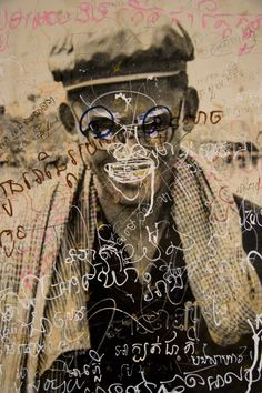 Photographs of Cambodians who worked for the Khmer Rouge at Security Prison 21 in 1975-1979, now defaced by the public.    Artist Vann Nath is one of only seven former prisoners of S21 to survive.    Prison photographer Nhem En also survived.