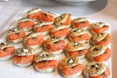 A variety of mini bagels, cream cheeses, fresh dill, cucumbers, capers, and red onion slivers.