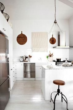 Modern kitchen with white countertops, silver appliances and wood highlights.