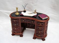 Kidney shaped Ornate writing desk Hand made from wood, the desk has carved detailing all around. The desk has 9 opening drawers Complete with leather upholstered chair. The desk has accessories
