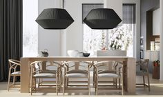 Wishbone chairs surround a blocky wood table, the clean lines and light forms balanced by bold oversized pendant lamps by Fabrice Berrux.
