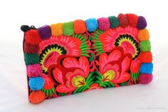 """Spread the happiness with this colourful choice of beautifully embroidered fabric Clutch Purses, with handmade cotton Pom Poms. This item is fully lined in black cotton, zip opening, a handy zip pocket insert and an added wristlet.Product dimensions are 11"""" x 6""""Any irregularities or imperfections in this product are part of the characteristics of the vintage fabric used."""