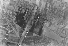 Damaged WW2 plane photographed mid-flight from above.
