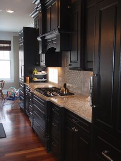 Black Cabinets with White Onyx Tile Blacksplash