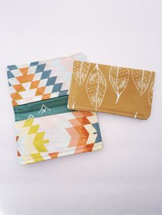"""Perfectly sized for credit cards, reward cards, gift cards, or just folded up cash! This is my go-to for keeping everything organized in my clutch or purse. Also, a great handmade touch for giving gift cards any time of year! Available in 5 different patterns:Succulent Tribal with Peachy Arrow PocketsMaize Feathers with Spring Aztec PocketsCoral Stripes with Mustard Floral PocketsWanderer Tribal with Charcoal Sketch PocketsSpring Aztec with Coral Arrow PocketsSizing:Approx. 4 1/4"""" x 2 ..."""