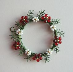 """Christmas Wreath pendant (2"""" outer diameter)    Craft wire, seed beads and miyuki drops.  I think I'm going to put this on Etsy, and if it hasn't sold within a month, I may well keep it.  I do love Christmas! :D"""