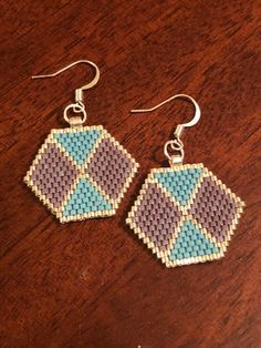 Each earring is hand woven using nylon thread and Delica glass seed beads. Colors : Plum, matte blue, and silver with nickel free silver ear wire Feel free to email if you like this style but would like to consider different colors. We will try to accommodate if possible.