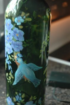 This is a hand painted wine bottle I did with lots of blue flowers and even a little blue bird on it.  SOLD