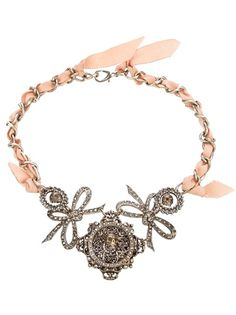Pink necklace from Cecilia Vintage featuring a silver-tone interwoven chain and ribbon and a front embellished with crystal encrusted skulls and bows. Please note that vintage items are not new and therefore might have minor imperfections.