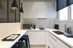 CHAMPS ELYSEES | Archipelles. PARIS Agency.  Modern kitchen interior architecture and design. Black and white kitchen. Simple and pure lines. Costum made countertop. Tolix Stools.