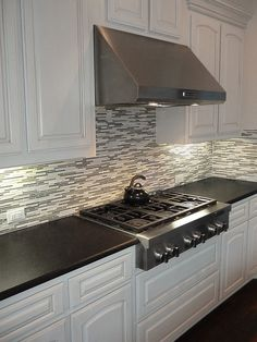 Black Pearl Leather Granite Countertops with a Mosaic backsplash and White painted cabinets