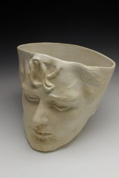 This simple pot has the face of a man sculpted into the side with a wide open mind for whatever you might like to place in it. Approximately 8 inches