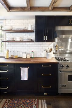 Material and element mix - white subway tiles, black cabinets, brass hardware, brushed chrome appliance, wood counter, shelves and beams. | kitchen design by Blair Harris