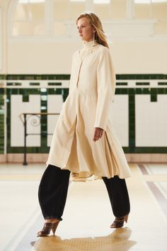 11. Coat dress in wool gabardine, high collar sweater in cotton crepe, large twisted pants in cotton denim, drop earring in silver and onyx, sandals in plastic