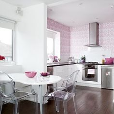 LOVE this kitchen - the subtle pink, the fun wallpaper, the lucite chairs, the dark counters and floors accented with white cabinets, walls, and table... LOVE it!