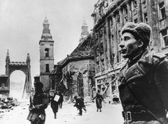 January 1945: A soldier stands in the snow by the damaged Inner City Church and the Elizabeth Church in Budapest in the last few months of WW II. (Photo by Keystone/Getty Images)