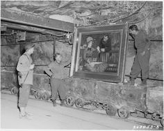 """American soldiers discover Manet's 'In the Conservatory' that was hidden (amongst other Nazi loot) in the salt mines of Merker, Germany. 1945."""