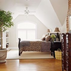 Attic Retreat...  Tall arched windows fill this reformed attic with light while a vaulted ceiling and built-in storage units maximize space. A soothing palette of neutrals is seen throughout the master suite and exposed chimney brick adds a punch of color and texture