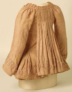 England 1780-90 sack-jacket, undyed cotton, roller-printed. Sack back with 10 narrow pleats ; fronts and cuffs edged with ruffle-frill trim in self fabric; divided stomacher front with 6 striped silk ribbon ties each side; peplum gathered at side waist with pocket openings; elbow length sleeves with ruffle-frill trim at cuffs and button with linen loop at inner edge; linen lining to waist, w/ back lacing. Hand stitched. belonged to Mrs David Garrick, wife of the actor.
