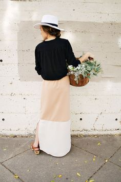 long color block white and peach skirt with a slit, loose thin black halfway sleeve pullover, with small white sun hat.