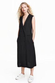 Jurk: Een lange jurk van zwaar vallende, structuurgeweven kwaliteit. De jurk heeft revers, een dubbele rij knopen en valse zakken. Ongevoerd.
