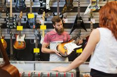 music store: music, sale, people, musical instruments and entertainment concept - assistant showing electric guitar to customer at music store
