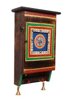 This ethnic rectangular box cum key holder is made of wood. It is adorned with warli paintings in the center and borders.   Can be used as a key ring holder as well as a decoration piece to beautify your house.   Bells at the bottom add to its ethnic look.