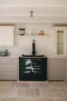 Our Light Tumbled Travertine looks great against that rich, green AGA and mushroom Shaker Kitchen from deVOL.