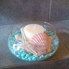 Un poco de mar en casa... Piedras celestes, caracoles, estrellas de mar y ostras combinadas con un relajante aroma a vainillas de la vela que es centro de este elemento de decoración que nos acerca al mar.