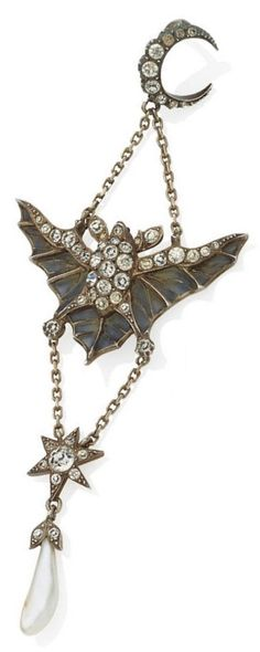 An Art Nouveau gold and diamond-set bat pendant, circa 1900. Designed as a bat with green plique-à-jour out-stretched wings, decorated throughout with circular paste, suspending a similarly-set star and freshwater pearl drop, to the paste-set crescent moon surmount, mounted in silver, 10cm long. #ArtNouveau #pendant