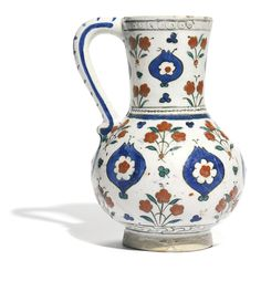 Iznik polychrome pottery ewer, Turkey, circa 1590, of baluster form, decorated in underglaze cobalt blue, green and relief red with black outlines, with a design of pomegranates containing flowerheads, floral blossoms in between, old collection label to underside 19.1cm. height. | sotheby's
