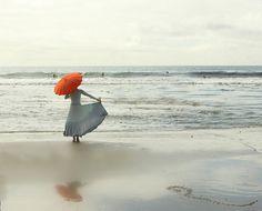 calm grey ~ vibrant red ~ the sea ~ a woman ~ an umbrella....silently fabulous