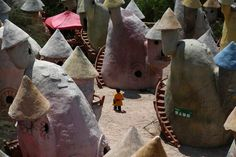A dwarf walks in between mushroom-shaped houses after his performances in <i>Kingdom of The Dwarves</i> at Kunming World Butterflies Garden, Yunnan province, China, May 21, 2014.