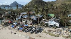 Death Toll In Phillipines Typhoon Could Reach 10,000 ---- An aerial view shows damaged houses, as residents wave for help after Typhoon Haiyan hit a village in Panay island