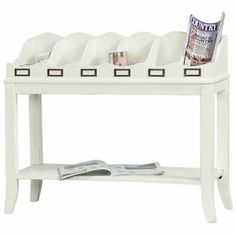 "Wood console table in distressed white with 6 top storage compartments and a bottom display shelf. Product: Console tableConstruction Material: Poplar solidsColor: Distressed whiteFeatures: Metal tag holders on frontRemovable dividersOne fixed shelfDimensions: 29"" H x 33"" W x 13"" D"