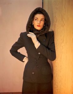 1946. Chocolat curve-button suit with nutria lined hood from Hattie Carnegie. Photo by John Rawlings