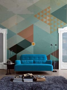 Geometric wallpaper, sea green and brown orange, bright blue chair, grey rug