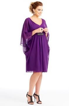Imitation silk knee-length dress.  This divine cape dress has a deep V-neckline and features metallic stud detailing centered at the bust.