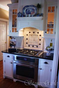 lit cabinets, backsplash, vent hood with shelf, dual fuel range